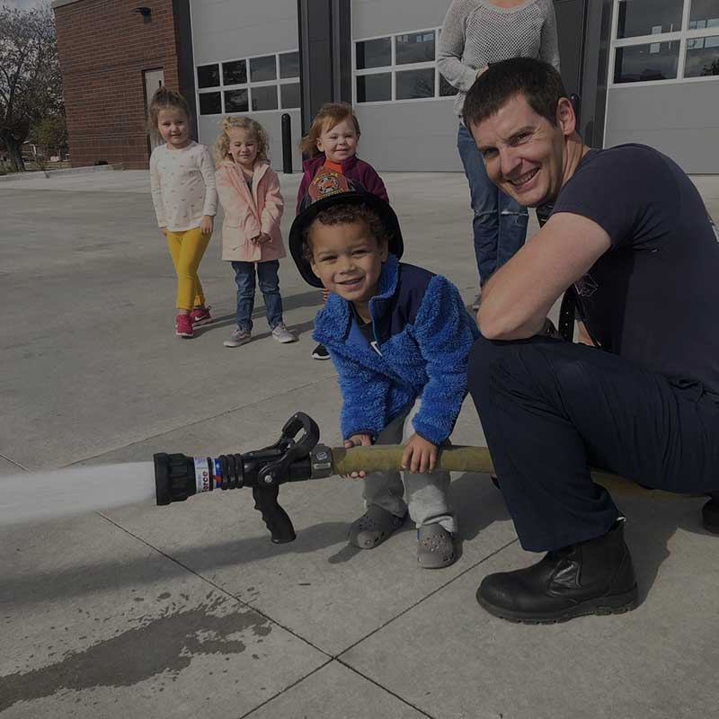 ACFR firefighter at a community event holding a firehose with a young child