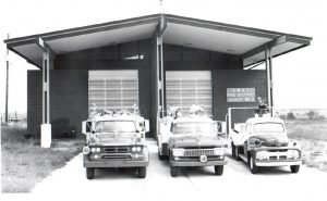 Black and white photo of old fire trucks in front of old station
