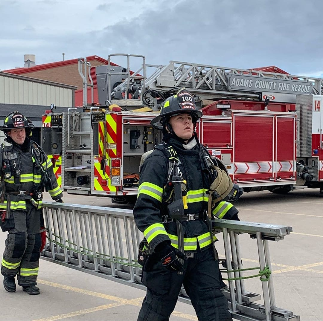 Two ACFR firefighters carry a ladder in front of an ACFR fire truck