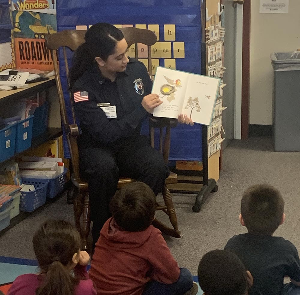 An ACFR employee reads a book to a class of children